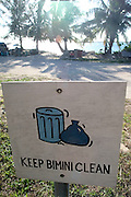 A hand-painted Keep Bimini Clean sign along a palm line street in the tiny Caribbean island of Bimini, Bahamas