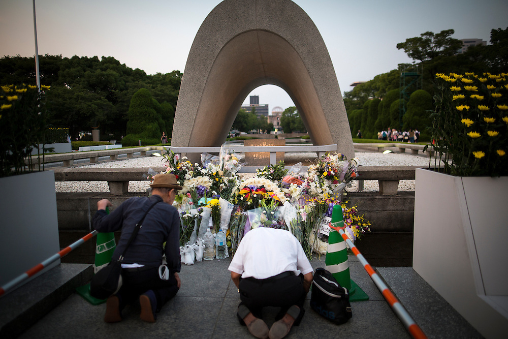 "HIROSHIMA, JAPAN - AUGUST 5 : Visitors lays flowers and pray for the atomic bomb victims in front of the cenotaph ahead of the 71st anniversary of the atomic bombing on Hiroshima at Hiroshima Peace Memorial Park in Hiroshima, western Japan, Friday afternoon, August 5, 2016. Japan marked the 71st anniversary of the atomic bombing on Hiroshima. On August 6, 1945, during World War II, the United States dropped a uranium gun-type atomic bomb named ""Little Boy"" on the city of Hiroshima which instantly killed an estimated 80,000 people, tens of thousands more would later die of radiation exposure. Three days later, a second American B-29 bomber dropped a plutonium implosion-type bomb ""Fat Man"" on Nagasaki, killing an estimated 40,000 people.  (Photo: Richard Atrero de Guzman/NURPhoto)"