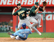 Second basemen Mark Ellis #14 of the Oakland A's makes a throw to first base after forcing out base runner Yuniesky Betancourt #3 of the Kansas City Royals, as shortstop Cliff Pennington #2 jumps out of the way in the fifth inning at Kauffman Stadium in Kansas City, Missouri. ..