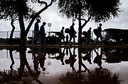 Texas Rangers are reflected in a rain puddle on their way to a spring training workout at the team's training facility on Sunday, February 19, 2017 in Surprise, Arizona. Players has limited workouts due to rain. (Ashley Landis/The Dallas Morning News)