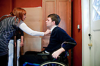 29 December, 2009. Bronxville, NY. Francesco Clark, 30, founder and president of Clark's Botanicals, is helped by his friend Patricia Margro to dress up in the garage of his home office where he exercises 5 hours every day. Francesco Clark suffers a crippling cord injury due to a swimming pool diving accident on June 1, 2002. Clark's Botanicals was born out of the tragedy.<br /> With his central nervous system impaired, Francesco, who was then an assistant stylist at Harper's Bazar, lost the ability not only to walk, but even to sweat. This led to clogged pores and chronic breakouts. When neither over-the-counter nor prescriptive remedies worked, he turned to his father, Dr. Harold Clark, a physician trained in both traditional Western medicine and homeopathy.<br /> <br /> Together they developed botanically-based formulas that effectively rebalanced Francesco's skin, clearing it up entirely. Through word-of-mouth, other people discovered and fell in love with these products, and in 2005, Francesco began selling Clark's Botanicals on his website.<br /> ©2009 Gianni Cipriano for The New York Times<br /> cell. +1 646 465 2168 (USA)<br /> cell. +1 328 567 7923 (Italy)<br /> gianni@giannicipriano.com<br /> www.giannicipriano.com