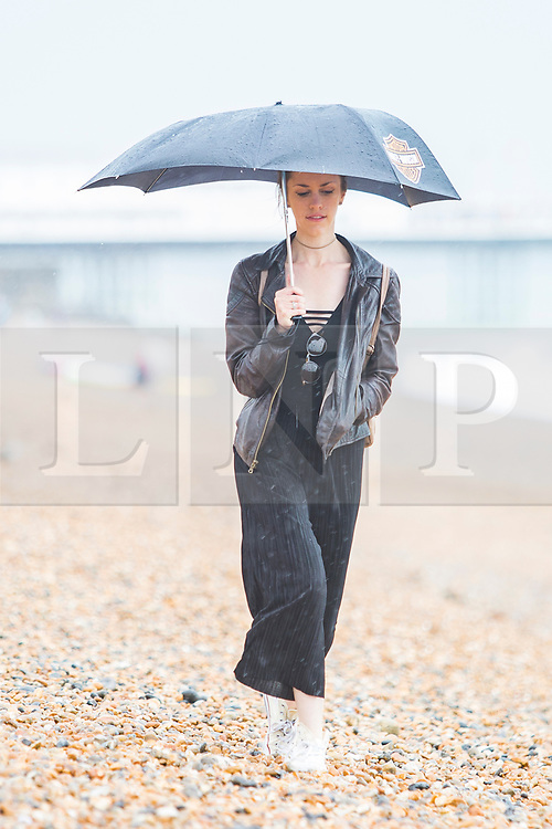 © Licensed to London News Pictures. 29/07/2017. Brighton, UK. Members of the public brave the wet weather to take some time out on the beach in Brighton and Hove. Photo credit: Hugo Michiels/LNP