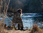 Unknown angler waits for a bite while trout fishing at the Blue River near Tishomingo, Oklahoma