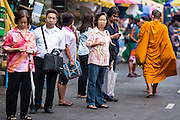 09 OCTOBER 2012 - BANGKOK, THAILAND: Buddhist monks walk past people waiting for a taxi in front of the Bangkok Flower Market. The Bangkok Flower Market (Pak Klong Talad) is the biggest wholesale and retail fresh flower market in Bangkok. It is also one of the largest fresh fruit and produce markets in the city. The market is located in the old part of the city, south of Wat Po (Temple of the Reclining Buddha) and the Grand Palace.    PHOTO BY JACK KURTZ
