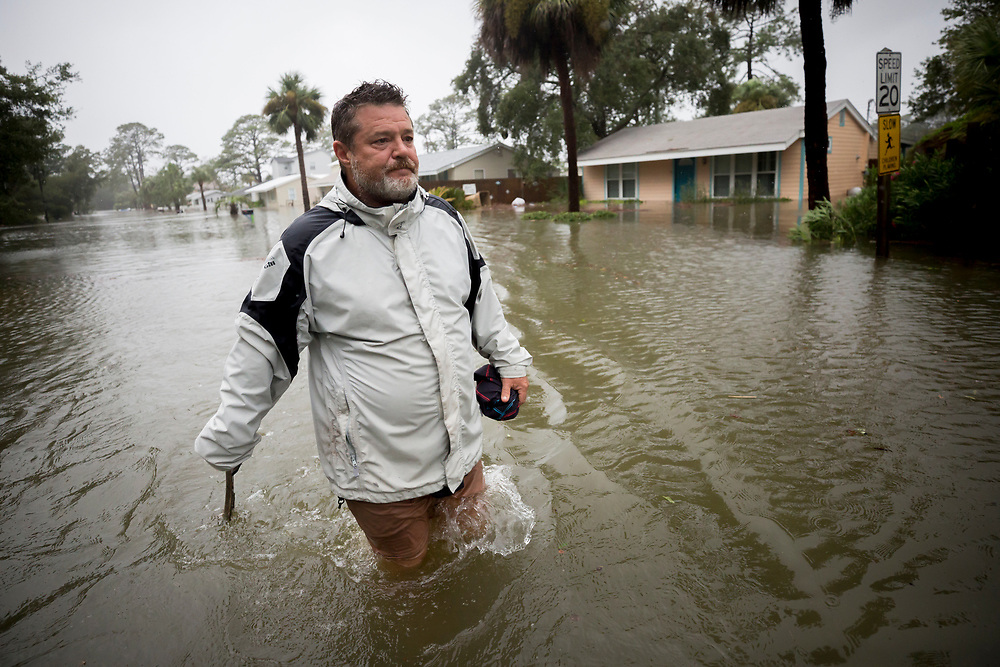 Joey Spalding walks back to his truck down the street where he lives, Monday, Sept., 11, 2017, on Tybee Island, Ga. Spalding just finished repairing his house from nine inches of water after Hurricane Matthew past the island last year. He said the Tropical Storm Irma brought three feet of storm surge into his living room today.  (AP Photo/Stephen B. Morton)