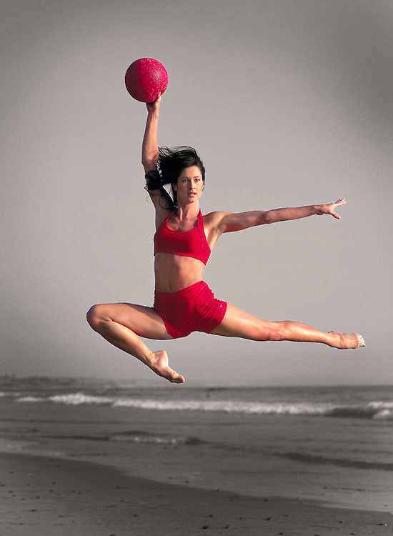 Girl leaping in air with Red Ball on Carlsbad State Beach in Carlsbad, CA