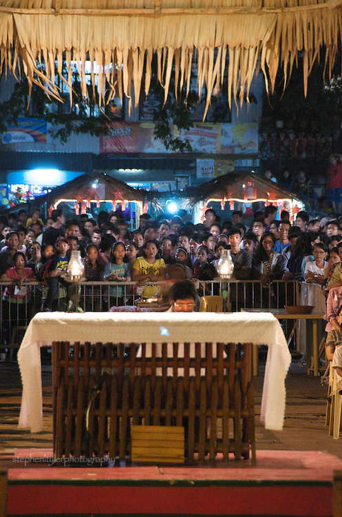 Followers gather outside of St. Joseph's Church of the Bamboo Organ in Las Pinas during Simbang Gabi, where nine straight nights of Mass is celebrated at 4 AM and leads up to a Midnight Mass on Christmas eve.