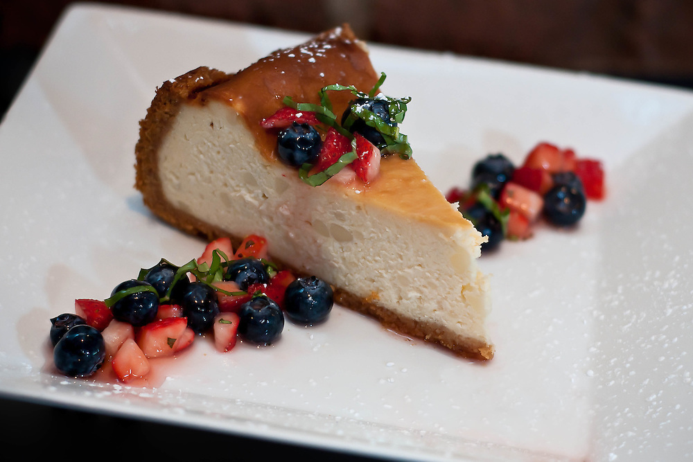 Creamy New York-style cheesecake with crushed berries and basil.