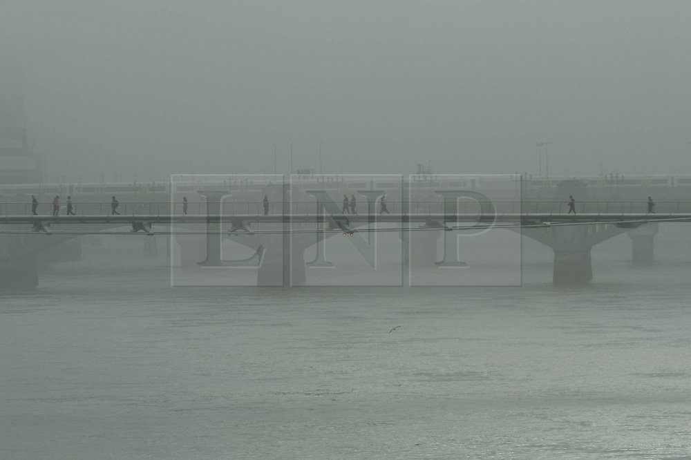 © Licensed to London News Pictures. 24/09/2013. London, UK. A heavy fog shrouds the River Thames between the Blackfriars, Millennium and and London Bridges as commuters make their way to work in the morning  across the Millennium Bridge.  Photo credit : Richard Isaac/LNP