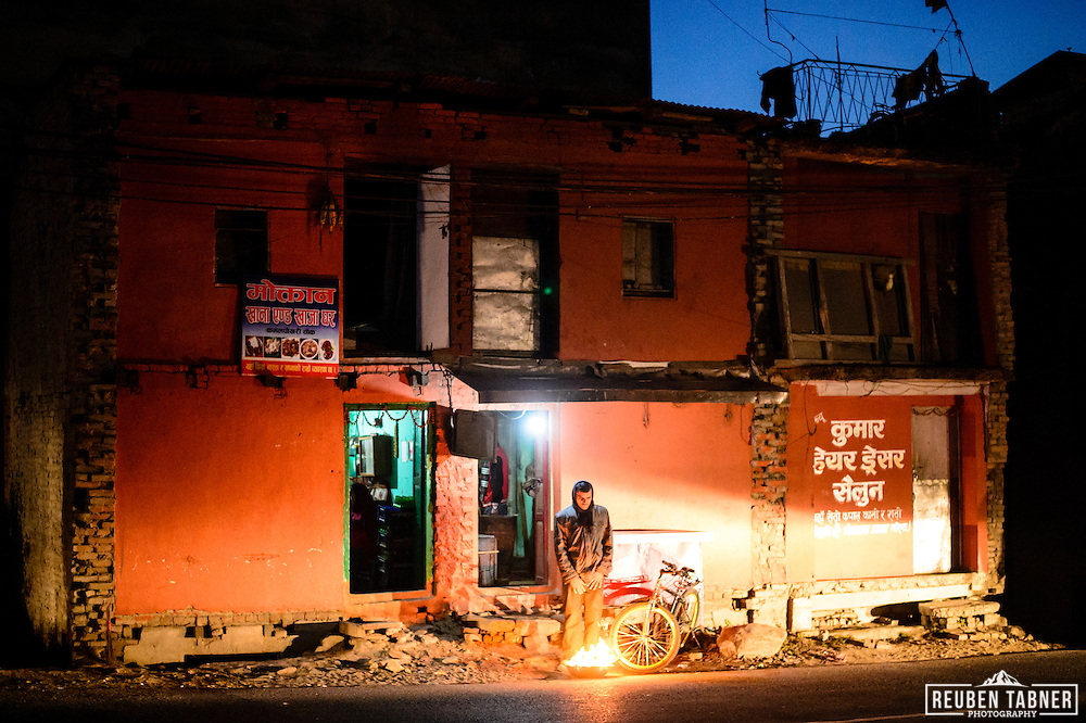 A man stands next to a street bonfire, outside a house in Kathmandu, Nepal.