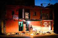 A man stands next to a street bonfire, outside a house in Kathmandu, Nepal.