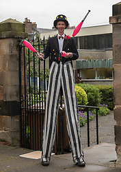 Pictured: Local juggler and stilt walker Michael Angelo Hanson welcomes people to the event<br /> <br /> The community in Portobello came out last night in support of a locally organised campaign to try and save a local church and its attached church hall for the community. No longer needed by the church, who plan to sell it, the hall is widely used by community groups. The campaign hopes to make use of Scottish community buy-out legislation that has recently been extended to cover urban areas in one fo the first such campaigns in a Scottish urban area. Local film acting couple, Shauna Macdonald and Cal MacAninch, were instrumental in the event that featured a variety of local talent and was attended by about 150 people, packing out the church hall. Shauna brought the show together, along with her sister Kyrsta, and Cal performed on stage in both the specially written short play that opened the evening and singing with the band Hooseband at the show's finale.  <br /> <br /> <br /> &copy; Jon Davey/ EEm