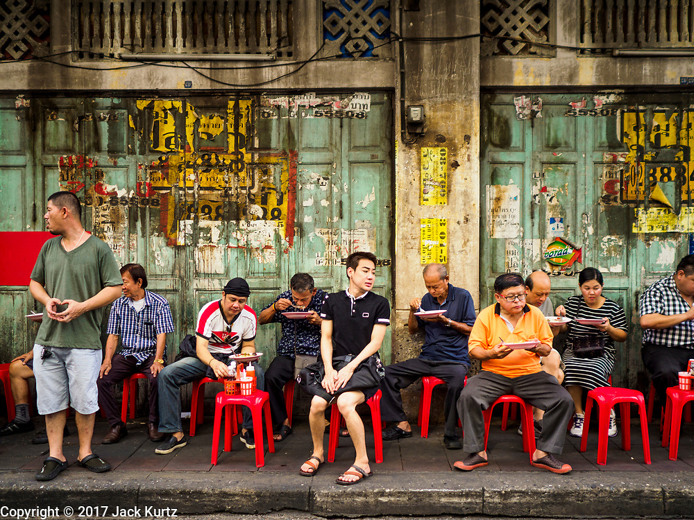 "18 MAY 2017 - BANGKOK, THAILAND: People sit on plastic stools and eat Thai curries at Jek Pui curry stand, a popular street food stall for curry dishes. City officials in Bangkok have taken steps to rein in street food vendors. The steps were originally reported as a ""ban"" on street food, but after an uproar in local and international news outlets, city officials said street food vendors wouldn't be banned but would be regulated, undergo health inspections and be restricted to certain hours on major streets. On Yaowarat Road, in the heart of Bangkok's touristy Chinatown, the city has closed some traffic lanes to facilitate the vendors. But in other parts of the city, the vendors have been moved off of major streets and sidewalks.      PHOTO BY JACK KURTZ"