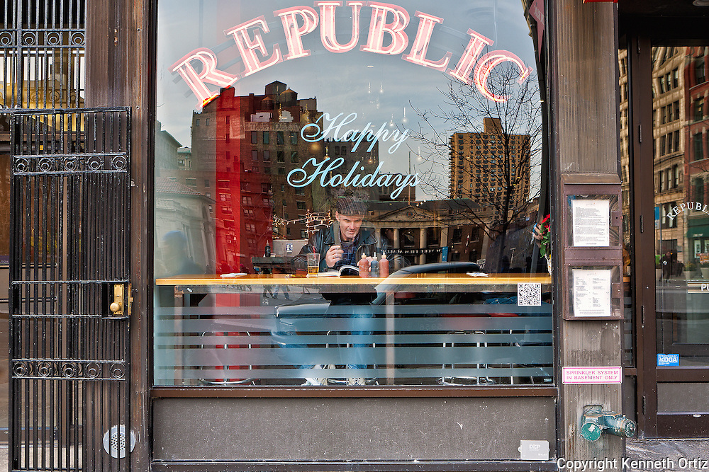 A Man reading his book and having a bite to eat at Republic restaurant by Union Square West.