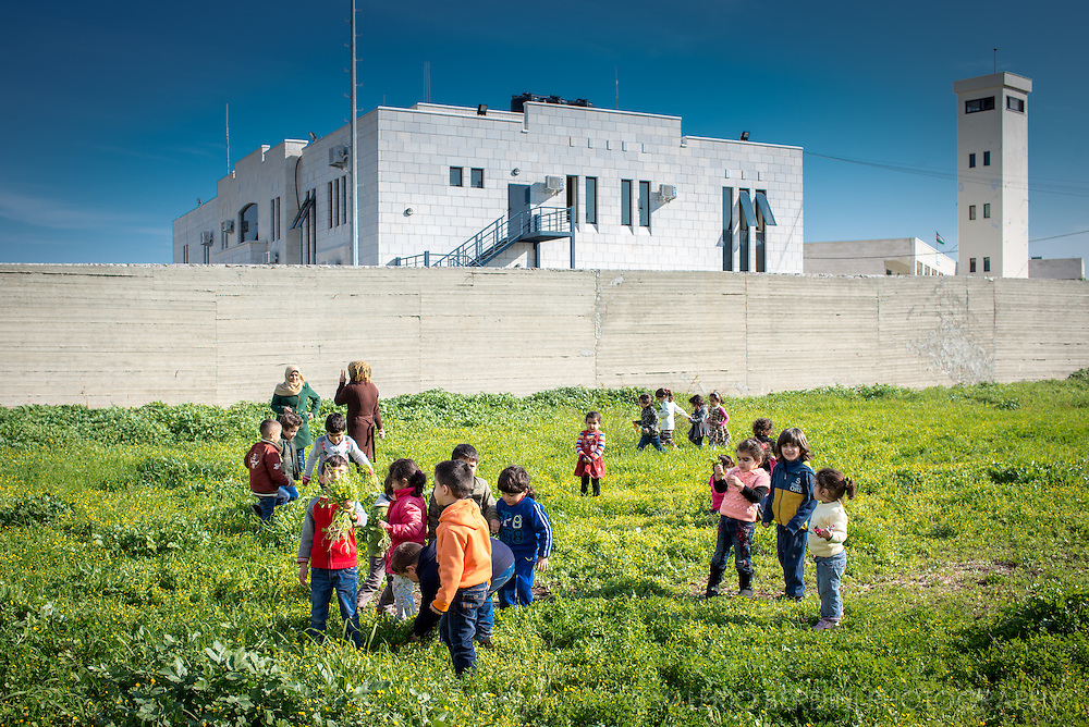 Pupils and teachers of a Jenin primary school pick flowers in a field next to a government building. They are part of one of the oldest refugee camps in Palestine, existing since 1948 to host thousands of Palestinians displaced by Israel in order to establish the State of Israel after the Second World War.