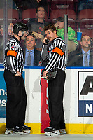 KELOWNA, BC - NOVEMBER 20:  With the play under review, referees Kyle Kowalski and Matt HIcketts stands at the timekeepers box awaiting a decision of whether or not the Sean Gulka #17 of the Victoria Royals scored a goal on Roman Basran #30 of the Kelowna Rockets prior to sliding into the net knocking it off its posts at Prospera Place on November 20, 2019 in Kelowna, Canada. (Photo by Marissa Baecker/Shoot the Breeze)