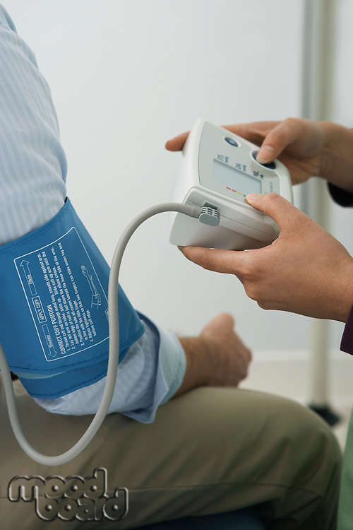 Doctor checking patients blood pressure,close-up