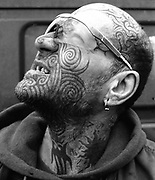 Close-up of man's tattooed face, wearing sunglasses, looking up, Bolonga,