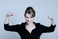 portrait of a young and cute one strong powerful woman flexing muscles proud on a studio isolated background
