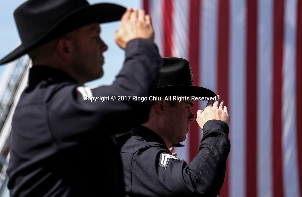 Police and firefighters salute as the hearse carrying the body of Whittier Police Officer Keith Boyer arrives at Rose Hills Memorial Park in Whittier, Calif., Friday March 3, 2017. Boyer, who was fatally shot after responding to a traffic crash, was remembered today by thousands of law enforcement officers, friends and family as a dedicated public servant, talented drummer, loving friend and even a ``goofy'' dad.(Photo by Ringo Chiu/PHOTOFORMULA.com)<br />