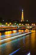 The Eiffel Tower at night and tour boat on the Seine River, Paris, France