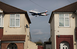 "© Licensed to London News Pictures. 27/10/2016. London, UK. A British Airways airliner is glimpsed between houses near Heathrow Airport as it lands. The government has announced that a third runway will be built at the United Kingdom's busiest airport. The Cabinet are divided - with Foreign Secretary Boris Johnson saying that the project is ""undeliverable"". Conservative MP for Richmond Zac Goldsmith has resigned. Photo credit: Peter Macdiarmid/LNP"