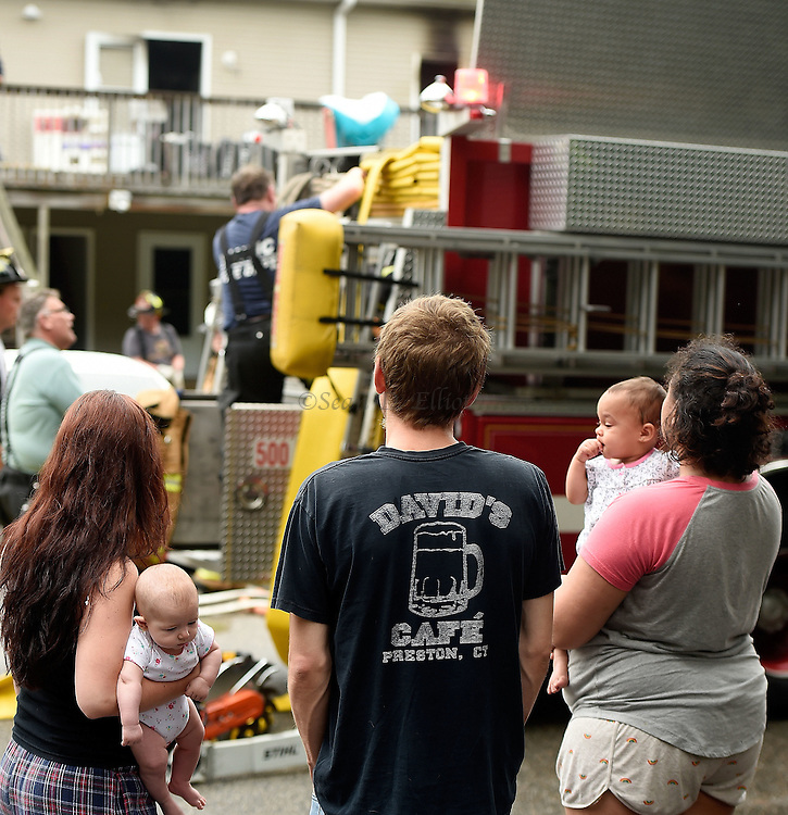 7/5/16 :: NEWS :: BOYLE :: Shannon Young, left, holds her four-month old daughter Madeline Trask as she and Madeline's father Dylan Trask, center, and nearby neighbor Kristina Cramer, holding her daughter Amelia, 11-months, watch firefighters clean up after extinguishing a fire at 17 Taftville-Occum Rd. in the Occum section of Norwich Tuesday, July 5, 2016. Nobody was injured in the blaze which began in the kitchen of unit 9 on the second floor of the building. Young and Trask live in unit 8 next door to the fire and Young was awakened by the tenants of unit 9 banging on her door to warn her of the fire. Mutual aid from Baltic, Yantic, Taftville and the Mohegan Tribal Fire Department assisted. . (Sean D. Elliot/The Day)