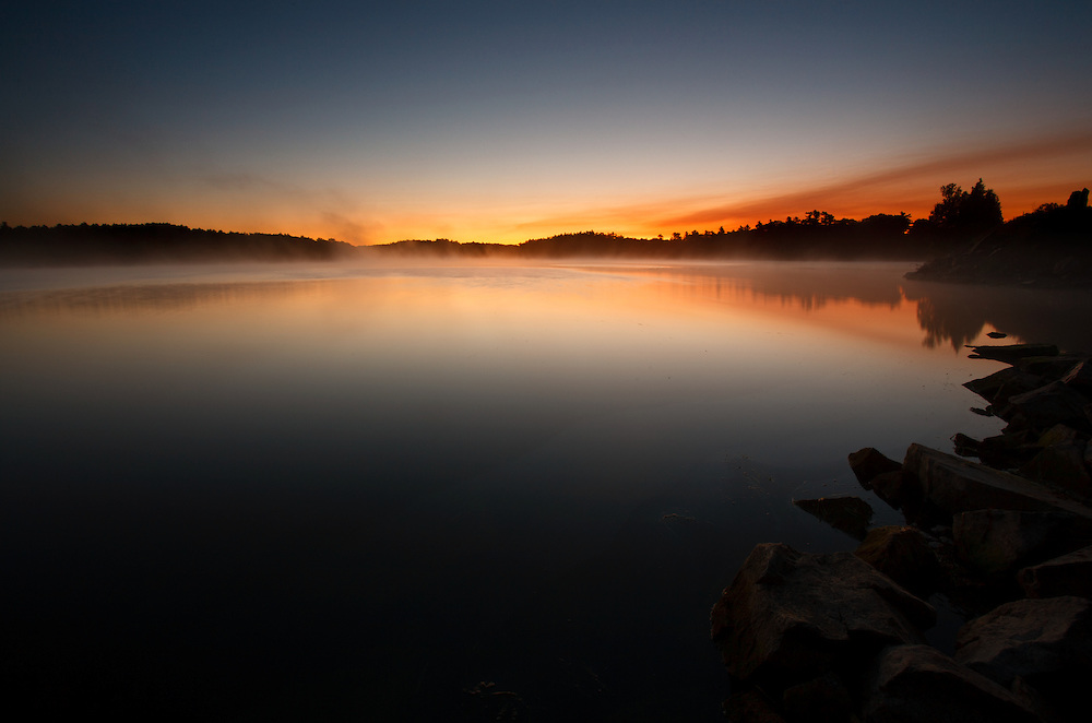 Intense Dawn glow on a small lake at the Thousand Islands St Lawrence River Ontario Canada