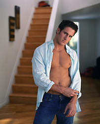 man with an open shirt rolling up his sleeve in a house