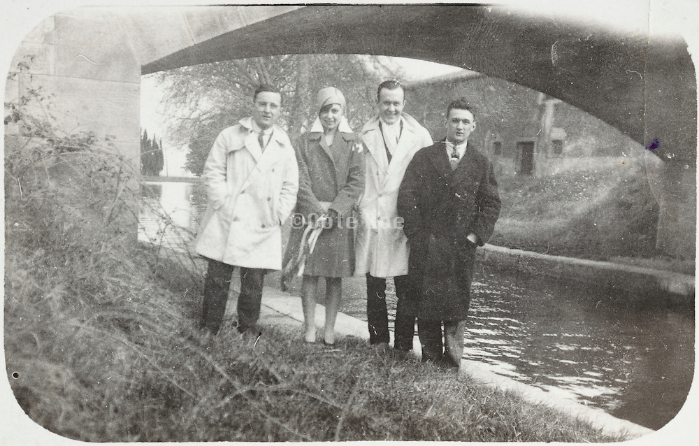 four adult people posing for an photo near a canal