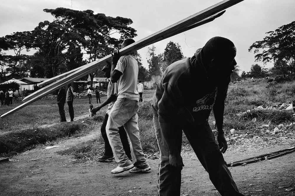 "NAIROBI, KENYA - OCTOBER 29, 2011: Kamau ""Kelly"" Ng'ang'a (right) carries building materials through the slum alongside his teammates. Athletes in the Kibera Olympic Boxing Club regularly volunteer their time working odd jobs secured for them by their coach, Hassan Abdulkadir Salim. Money raised is then used for transportation, competition entry fees and new equipment.<br />
