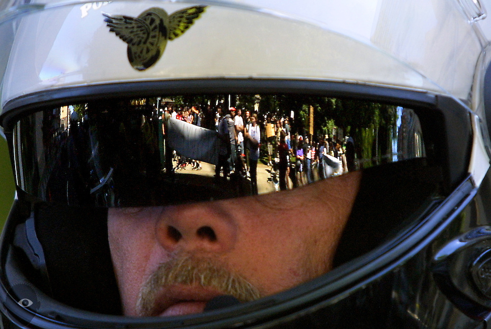 Reflected in the shield of a Portland Police motorcycle officer, protestors take to the streets about the Federal Courthouse to show their displeasure of the visit of U.S. Attorney John Ashcroft.