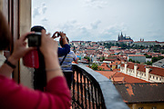 Tourists enjoying the View from the Jesuit College Clementinum Tower towards the Lesser Town (Mala Strana) and Prague Castle.