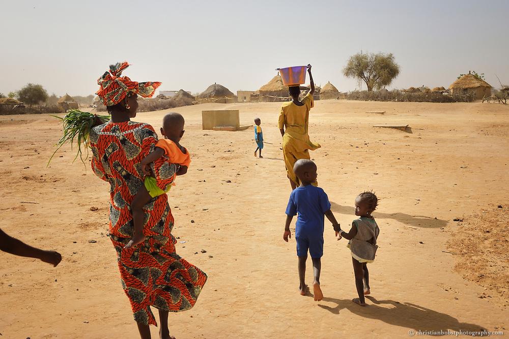 Dank eines von HEKS mitfinanzierten Bohrbrunnen können Frauen im sehr heissen und trockenen YOUNOUFERE in Senegal einen Garten anlegen und  Gemüse anbauen. Das Bild zeigt Frauen auf dem Heimweg vom Garten.