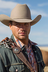 portrait of a good looking rugged cowboy outdoors