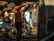 12 NOVEMBER 2015 - BANGKOK, THAILAND:  A demolition worker uses a cutting torch to tear down a home at Wat Kalayanmit. Fifty-four homes around Wat Kalayanamit, a historic Buddhist temple on the Chao Phraya River in the Thonburi section of Bangkok, are being razed and the residents evicted to make way for new development at the temple. The abbot of the temple said he was evicting the residents, who have lived on the temple grounds for generations, because their homes are unsafe and because he wants to improve the temple grounds. The evictions are a part of a Bangkok trend, especially along the Chao Phraya River and BTS light rail lines. Low income people are being evicted from their long time homes to make way for urban renewal.       PHOTO BY JACK KURTZ