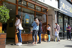 "© Licensed to London News Pictures. 24/05/2020. London, UK. People queue outside 'ANTEPLIER BAKLAVA' a Turkish restaurant on Green Lanes, Haringey in north London which is open for take away only due to coronavirus lockdown, as Muslims celebrate Eid al-Fitr. On Eid al-Fitr also known as ""Festival of Breaking the Fast"", a religious holiday celebrated by Muslims worldwide that marks the end of the month-long fasting of Ramadan, restaurants would normally be packed with people celebrating Eid. Photo credit: Dinendra Haria/LNP"