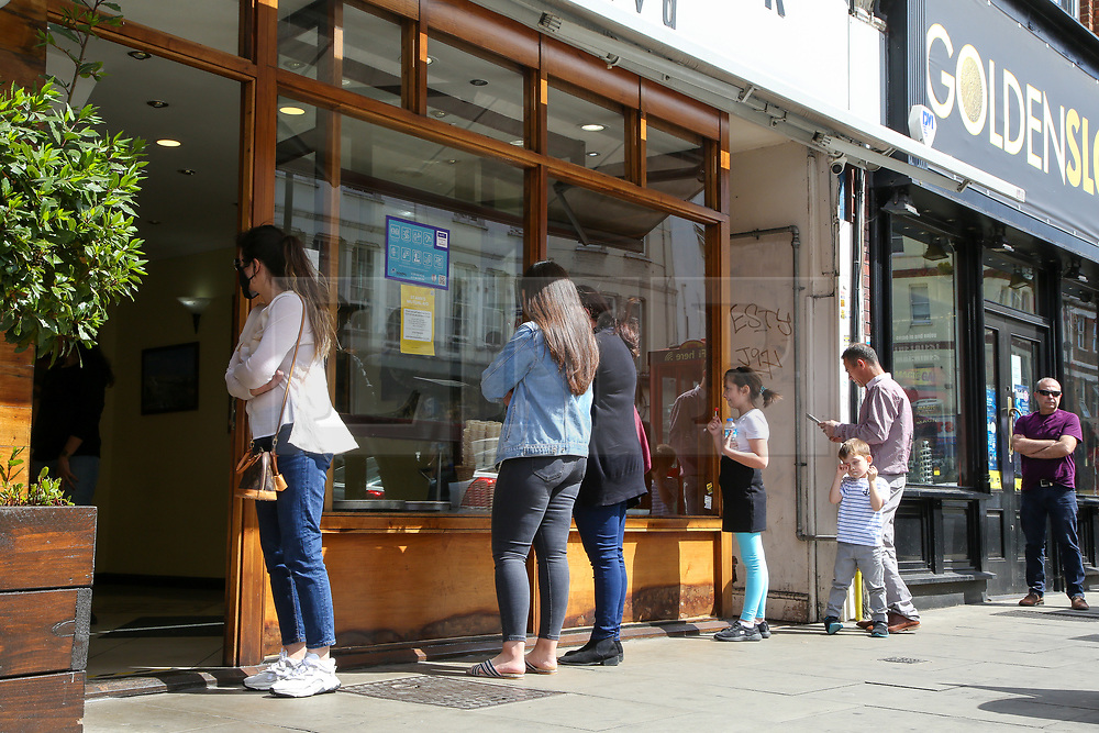 """© Licensed to London News Pictures. 24/05/2020. London, UK. People queue outside 'ANTEPLIER BAKLAVA' a Turkish restaurant on Green Lanes, Haringey in north London which is open for take away only due to coronavirus lockdown, as Muslims celebrate Eid al-Fitr. On Eid al-Fitr also known as """"Festival of Breaking the Fast"""", a religious holiday celebrated by Muslims worldwide that marks the end of the month-long fasting of Ramadan, restaurants would normally be packed with people celebrating Eid. Photo credit: Dinendra Haria/LNP"""