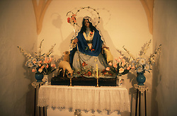 Statue of Virgin Mary with lambs and flowers in church in Ardales; Andalucia,
