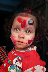A portrait of a baby girl in Holi festival in the street of Shakhari Bazaar, Dhaka, Bangladesh on 21, March'2019.