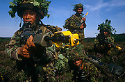Four members of the Royal Gurkha Rifles are on tactical manoeuvres on heathland above Farnborough airfield, England. These Nepali-born boys belong to an elite Regiment of the British army. Every year 60,000 boys attend recruiting sessions in villages and towns in the Himalayan Kingdom but only 150 are selected each year to serve on active duty across the world. They fly to the UK for basic soldier training where they learn the skills required for infantry, transport, communications or clerical duties. Their reputation as a fierce but intensely loyal fighting force and many Victoria Crosses were won for bravery during World War 2. Here they are seen cradling modern SA-80 rifles while dressed in camouflaged helmets with oak leaves. The nearest to the camera points his weapon past the viewer with a yellow blank cover attached. .