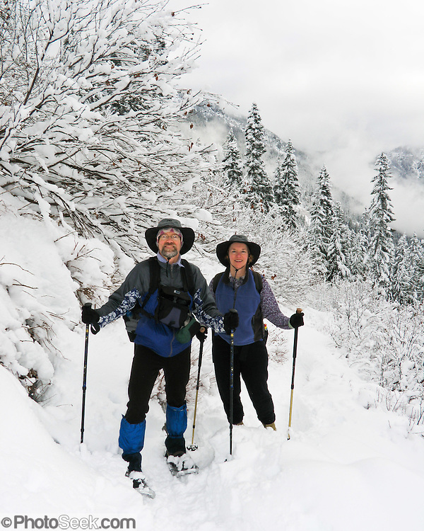 A man and woman snowshoe through forest on the Snow Lake trail in early December at Snoqualmie Pass, Washington, USA For licensing options, please inquire.