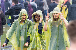 © Licensed to London News Pictures . 07/06/2014 . Heaton Park , Manchester , UK . Revellers traipse through rain and mud . The Parklife music festival in Heaton Park Manchester following heavy overnight rain . Photo credit : Joel Goodman/LNP