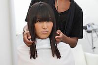 Asian woman getting a new haircut at beauty salon