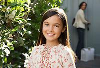 Girl smiling head and shoulders mother locking door in background