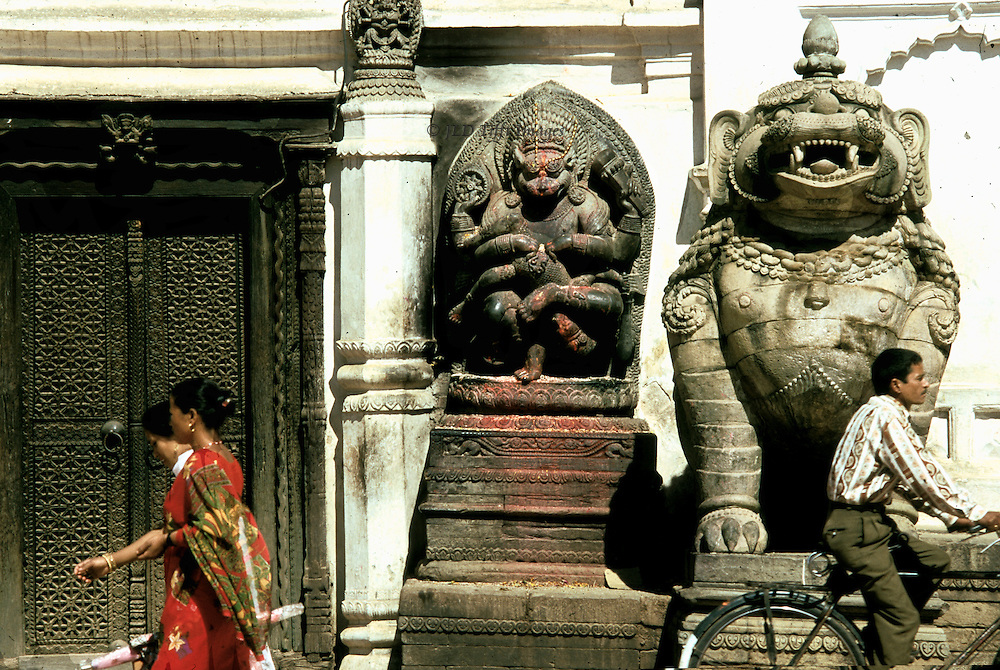 Outside the Lion Gate in Durbar Square, stone statue of a ferocious lion; behind it and to the left, a stone carving of Ugrachandi, the god Shiva's consort in her fearful manifestation.  Man passes right on a bicyle; two Nepali women walk by on the left.