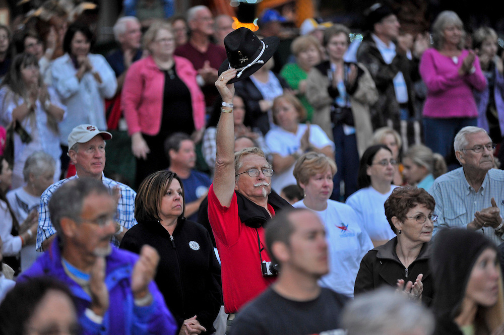 A person in the crowed raising his US Cavalry hat in honor of the The Wounded Warriors Marines coming in. Lt. Dan Band Weekend2 Beaufort, South Carolina. Sep 16, 2011.