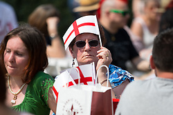 © Licensed to London News Pictures. 21/04/2018. London, UK. A woman covers her head with a English Flag during hot weather at the 'Feast of St George' event in Trafalgar Square, to celebrate the Patron Saint of England. St George's Day is on 23 April. Photo credit : Tom Nicholson/LNP