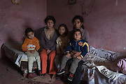 Roma mother with children in their temporary home in a communist-era barn which the authorities of the town of Roman in Romania have partitioned into sleeping quarters for homeless Roma.