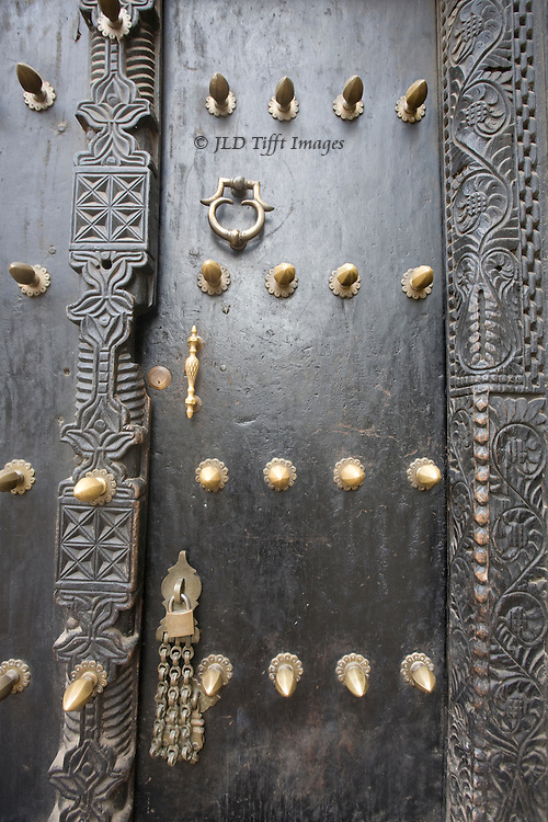 Stonetown door of wood studded with large brass nail heads.
